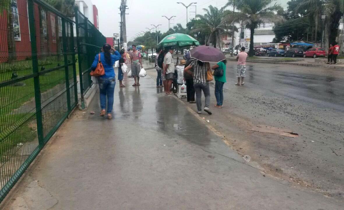 Sem abrigo, os usuários do transporte coletivo enfrentam sol, chuva e lama onde o Grupo DB deixou de construir a para de ônibus (Foto do Leitor)