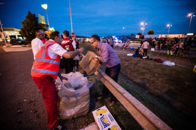 Hungary: Budapest, 4 September 2015 In response to hundreds of refugees and other migrants taking to the road with the aim of walking to Austria, Hungarian Red Cross immediately activited its response teams. The Red Cross has been providing food, water, blankets, clothes and first aid to those in need along the main highway from Budapest to Austria. Over 140,000 people have applied for asylum in Hungary already in 2015. In recent weeks, the number of people arriving in the country has increased dramatically, resulting in a major bottle neck and leaving hundreds sleeping rough at train stations each night. Photo: Stephen Ryan / IFRC