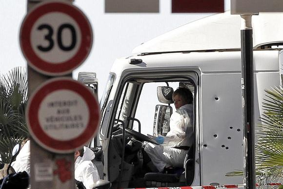 Policiais investigam a cabine do motorista do caminhão que se jogou sobre uma multidão de pessoas que comemoravam a data nacional da França, em NiceAlberto EstevezPoolAgência Lusa