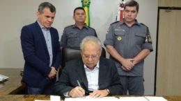 Governador Amazonino Mendes assina promoção de policiais militares observado por secretário de Segurança, Bosco Saraiva, e comandante da PM, David Brandão (Foto: Clóvis Miranda)