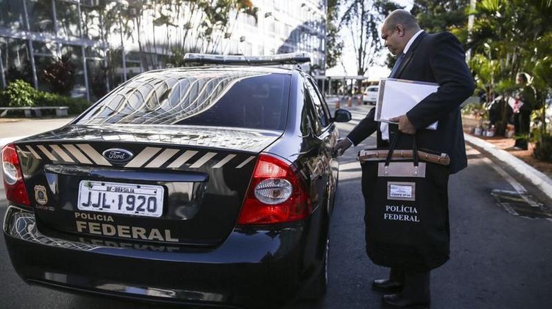 Agente da Polícia Federal recolhe documentos em nova fase da Operação Registro Espúrio (Foto: José Cruz/ABr)