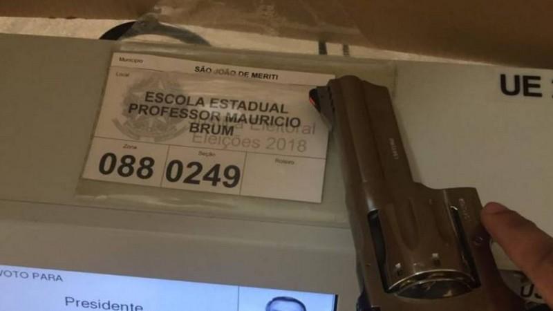 Arma aparece em cima de uma urna na Escola Estadual Professor Mauricio Brum, em São João do Mereti, no Rio de Janeiro (Foto: Twitter/Reprodução)