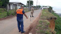 Técnico da Defesa Civil inspeciona trecho da rua que corre risco de desmoronar devido à erosão (Foto: Defesa Civil/Divulgação)