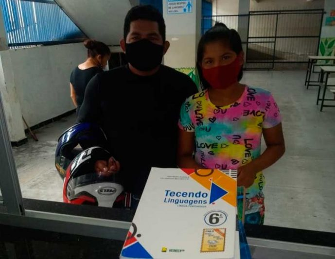 Acompanhada do pai, aluna devolve livros didáticos (Foto: Eliton Santos/Semed)