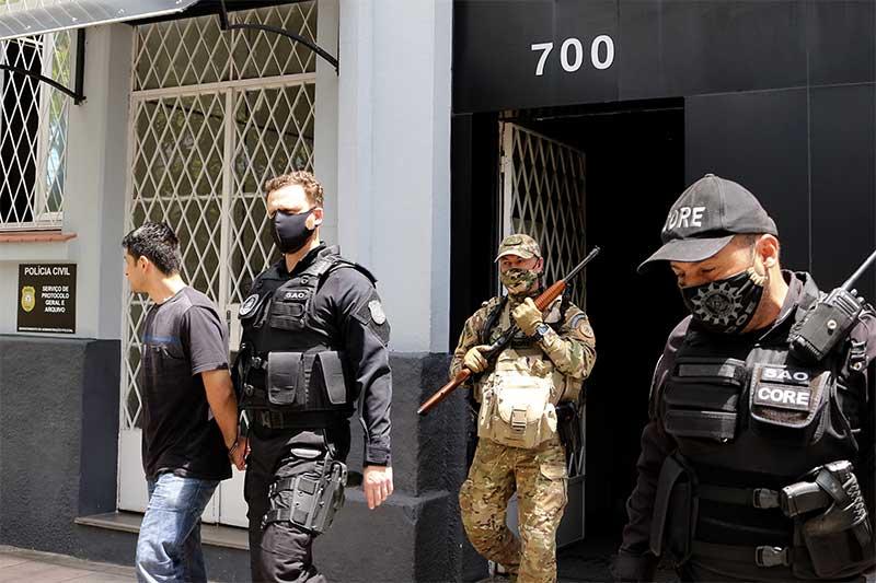 Segurança do Carrefour é escoltado por policiais ao deixar delegacia (Foto: Miguel Noronha/Agência-F8/Folhapress)