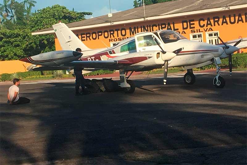 Piloto (de joelhos) foi preso e avião ea droga apreendidos (Foto: Polícia Militar/Divulgação)