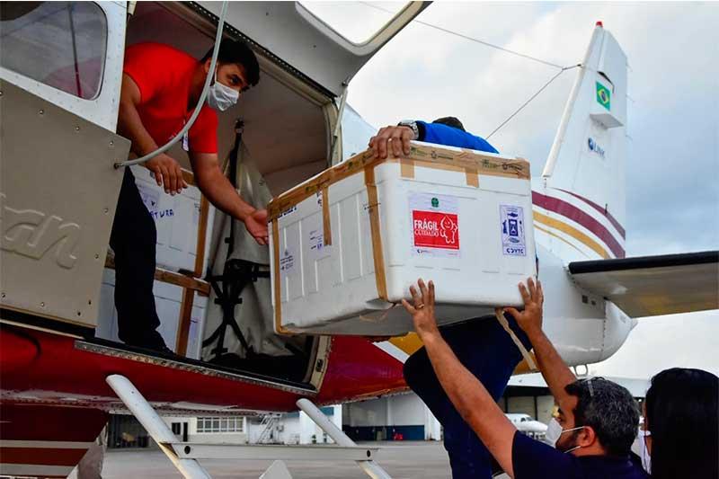 Caixa com vacina é embarcada em avião para o interior (Foto: Mauro Neto/Secom)