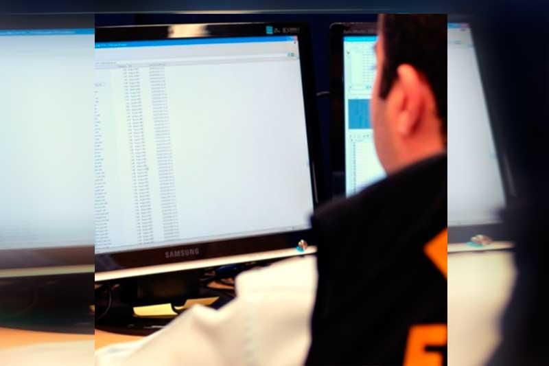 Agente da PF inspeciona computador apreendido com hacker (Foto: PF/Divulgação)