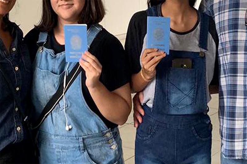 Irmãs exibem passaporte após adoção em Manaus (Foto: Acervo familiar/Divulgação)